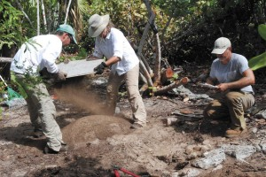 Researchers on Ft. George Cay screen soil from the test excavation site.