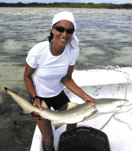 Marta Calosso holds a young lemon shark prior to tagging in the waters off South Caicos.