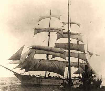 The Norwegian barque Stifinder is under sail with casual German submariners in the foreground.
